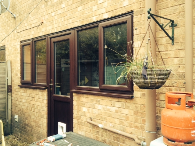 New replacement windows and door in a dark wood-effect finish